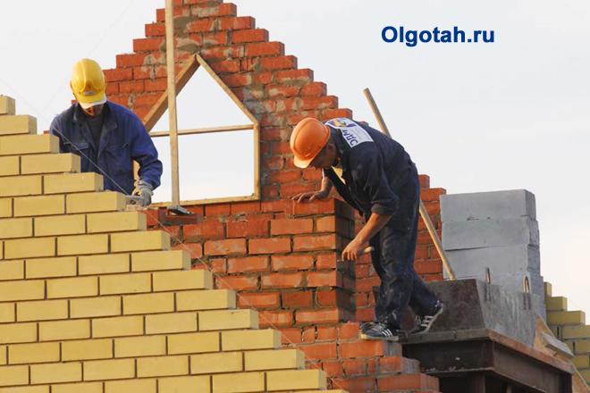 Рабочие выкладывают стену дома из кирпича