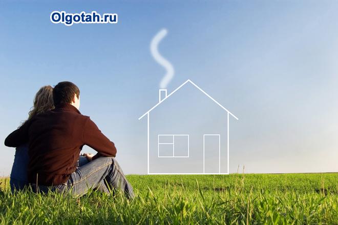 Молодая пара сидит на траве и мечтает о своем доме