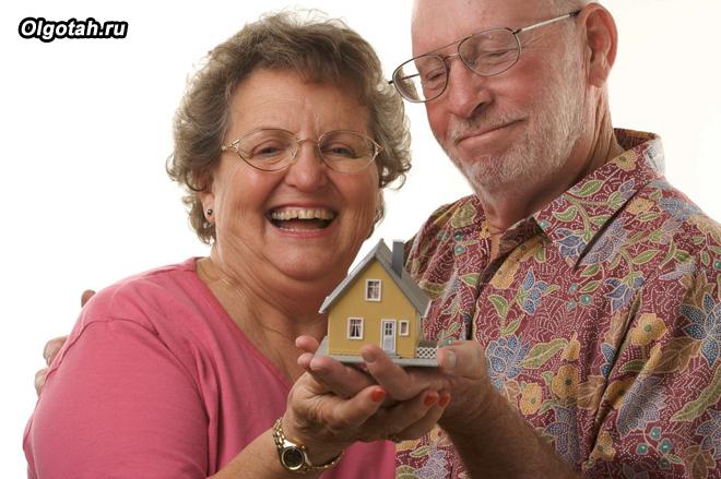 Довольные пенсионеры держат в руках игрушечный домик