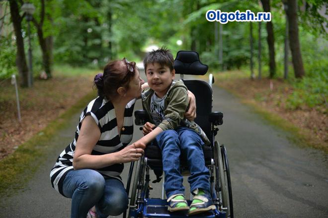 Мама гуляет с сыном-инвалидом в парке