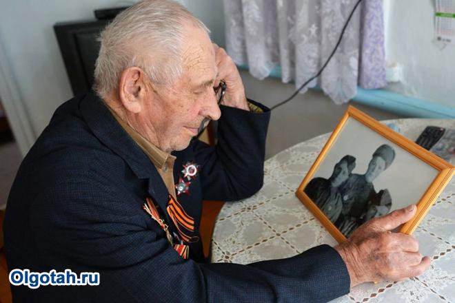 Пенсионер смотрит на старую фотографию в рамке
