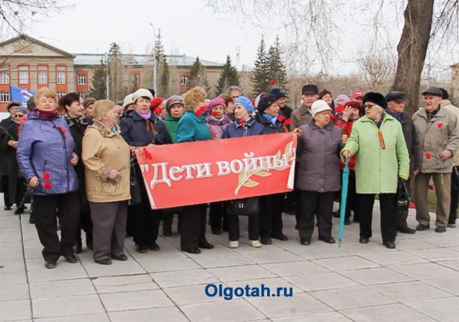"""Митингующие стоят с плакатом """"Дети войны"""""""