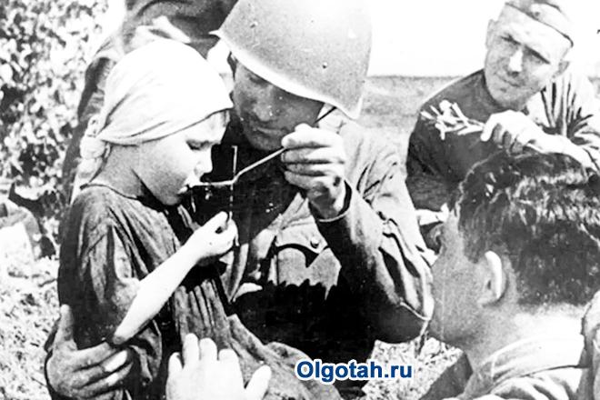 Советские солдаты кормят девочку