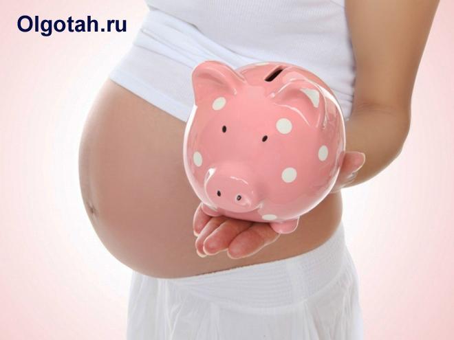 Беременная девушка держит в руке копилку-хрюшку