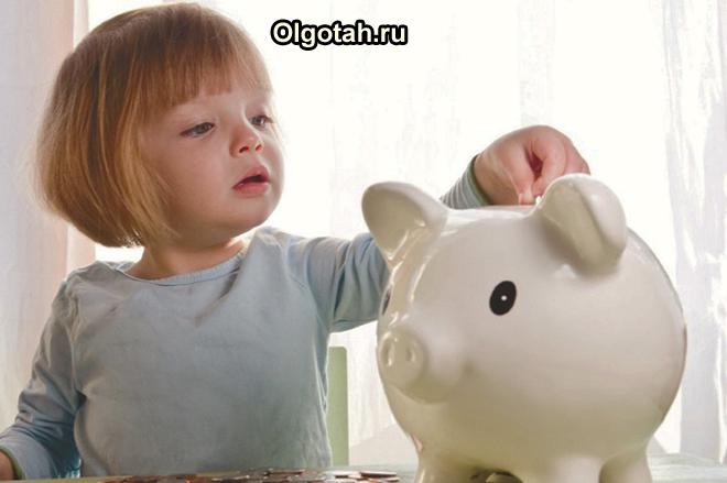Девочка кладет монетку в копилку-хрюшку