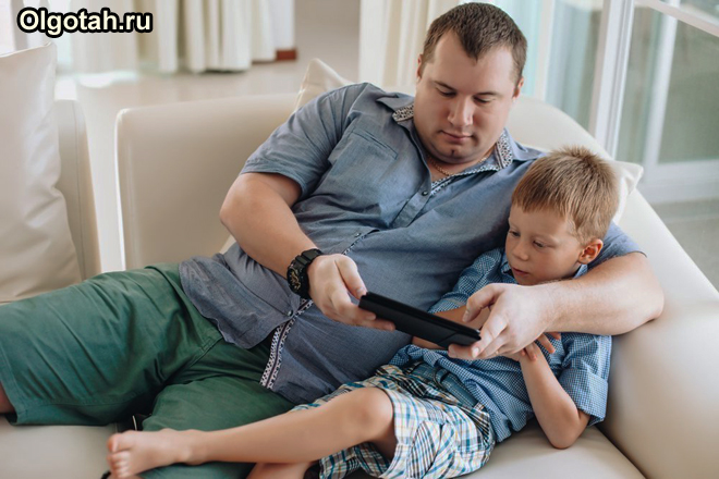 Папа с сыном играют вместе на диване в игру на планшете