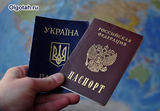 Человек держит в руке украинский и российский паспорта