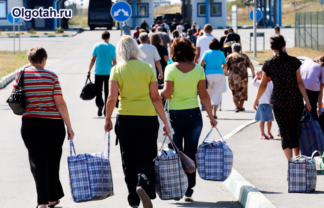 Люди идут с вещевыми сумками по улице