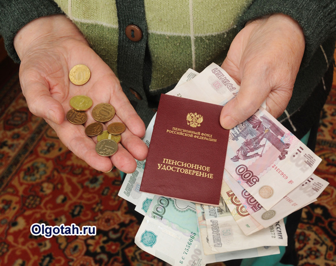 Бабушка держит в руке пенсионное удостоверение и деньги