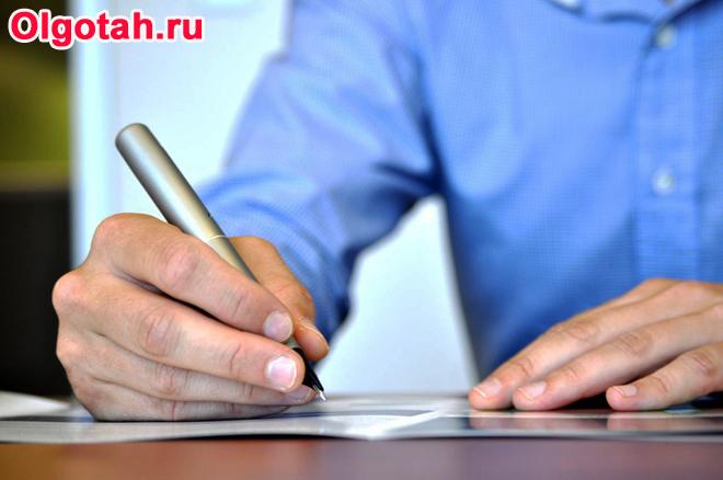 Мужчина в синей рубашке пишет в тетради