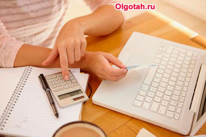 Девушка сидит за ноутбуком, в руке держит банковскую карточку