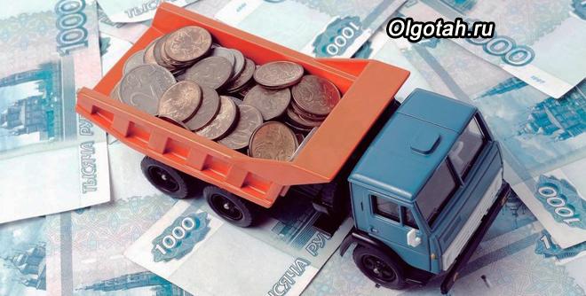 Игрушечный грузовичок с монетами стоит на тысячных купюрах