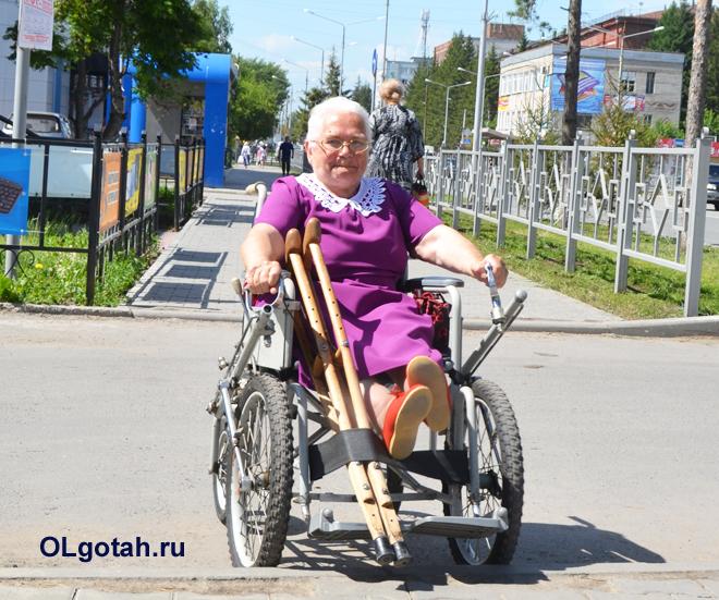 Пенсионерка в инвалидном кресле на прогулке
