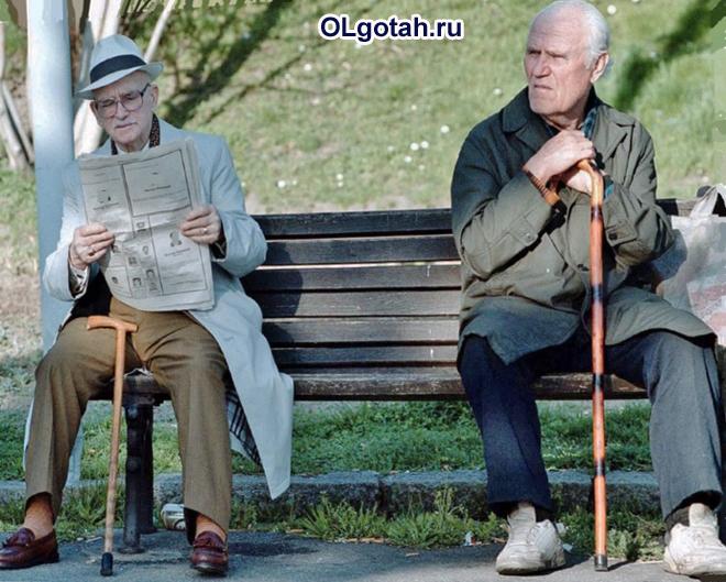 Пенсионеры сидят в парке на лавочке