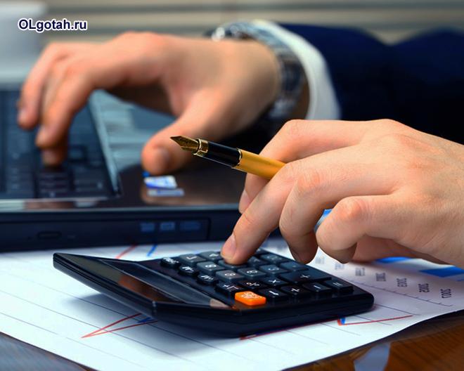 Бизнесмен считает на калькуляторе прибыль