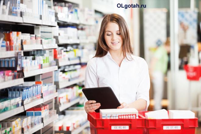 Фармацевт раскладывает лекарства по полочкам