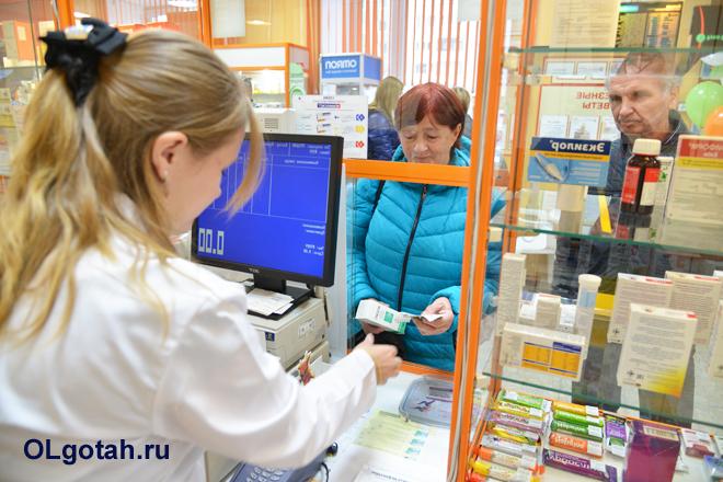Фармацевт продает лекарства покупателям