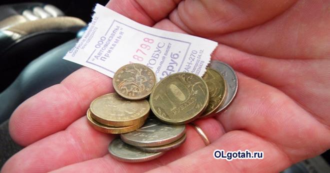 Пассажир держит в руке деньги и билет