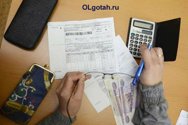 Человек считает сумму по квитанциям