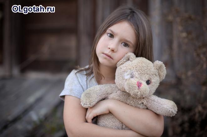 Грустная девочка держит игрушечного мишку в руках