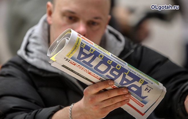 Мужчина читает в газете про работу