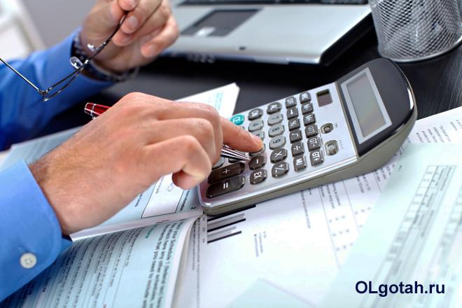 Бизнесмен считает свою выручку на калькуляторе
