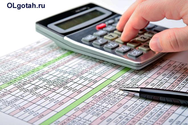 Бизнесмен пересчитывает на калькуляторе таблицы с листа