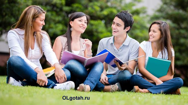 Студенты сидят на лужайке с учебниками и общаются