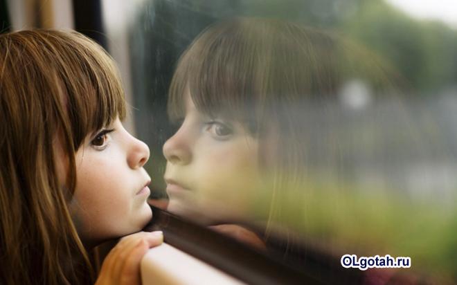 Грустная девочка смотрит в окно