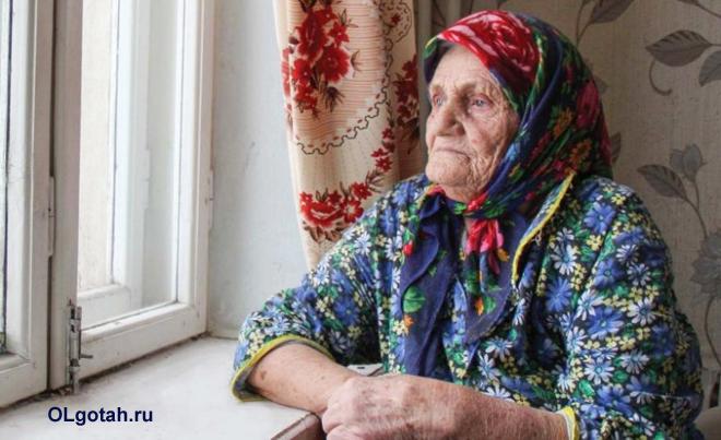 Бабушка сидит и смотрит в окно