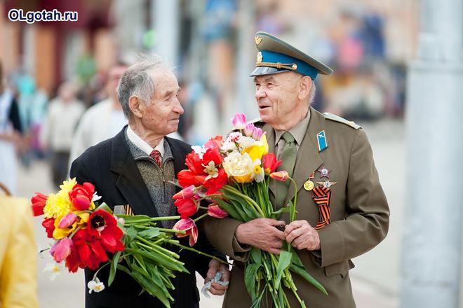 Ветераны ВОВ держат в руках цветы