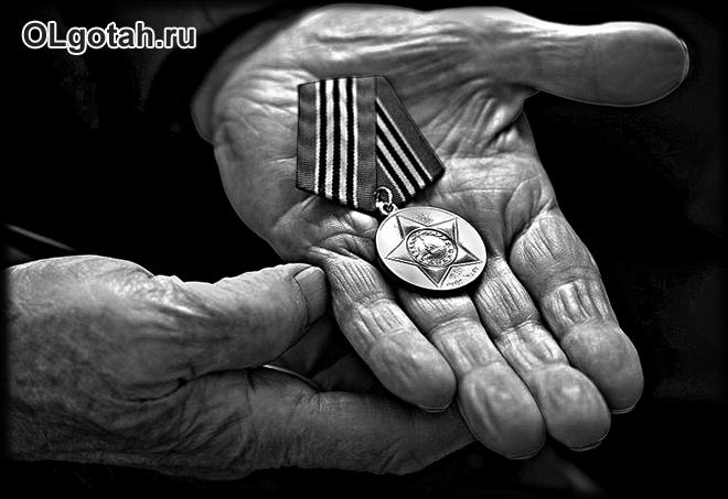 Ветеран ВОВ держит в руке медаль