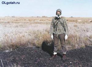 Человек в маске стоит в поле