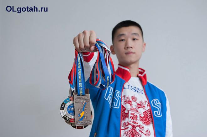 Спортсмен держит свои медали в руке