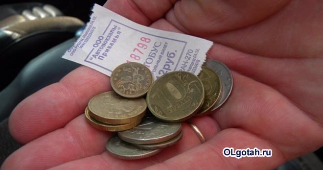 Человек держит в руке деньги на проезд