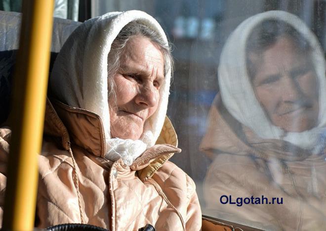 Пенсионерка едет в автобусе и смотрит в окно