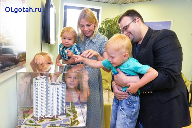 Многодетная семья рассматривает макет будущего дома