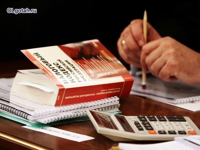 Человек сидит за столом, рядом лежит налоговый кодекс, калькулятор