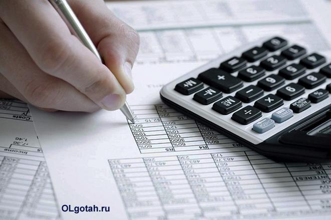 Бухгалтер считает данные таблиц на калькуляторе