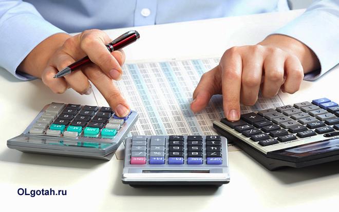 Бизнесмен считает содержимое таблиц на калькуляторах