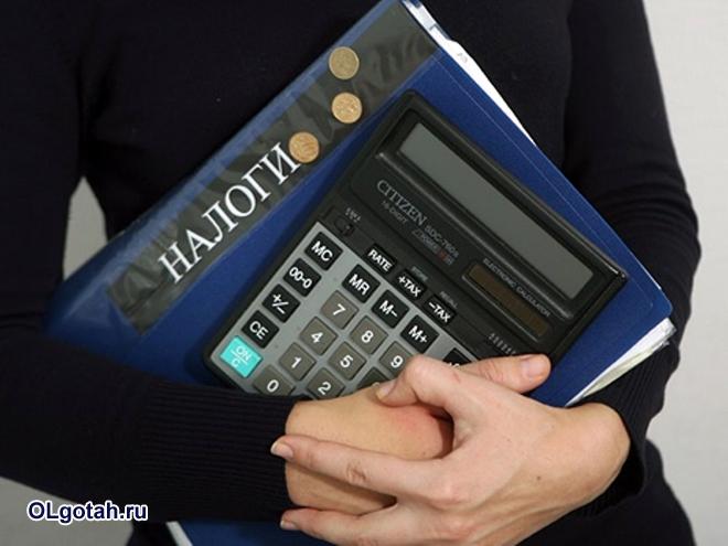 Девушка держит папку с надписью налоги и калькулятор