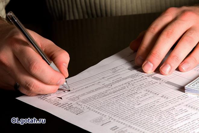Человек подписывает бумагу