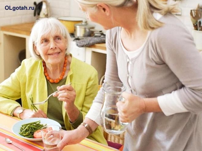 Пожилую женщину кормят ужином