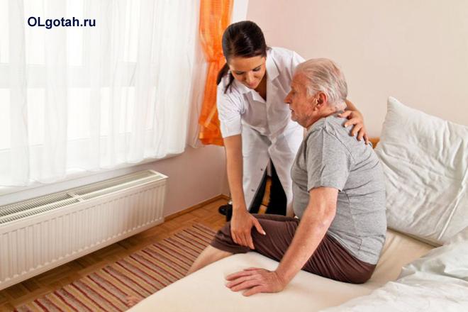 Пожилому мужчине помогают встать с кровати