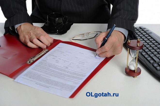 Бизнесмен подписывает документацию