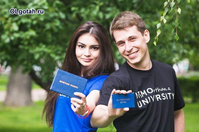 Девушка и парень держат в руках зачетки