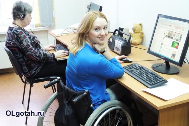 Девушка-инвалид принимает работает за компьютером