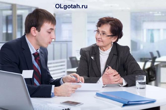 Молодой человек и пенсионерка разговаривают в офисе