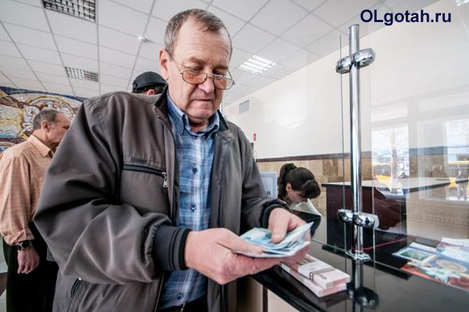 Пенсионер пересчитывает деньги, полученные в банке