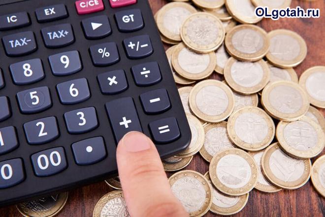Человек пересчитывает деньги на калькуляторе